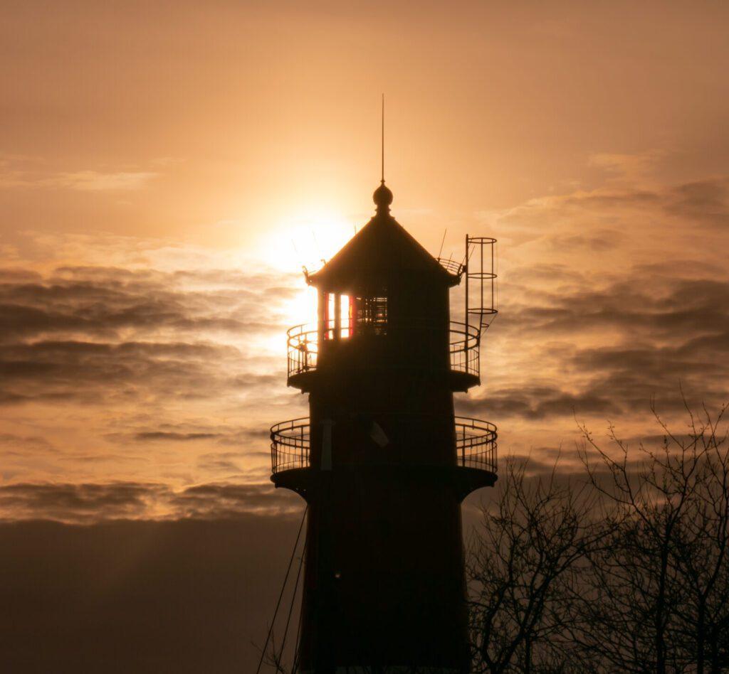 Nordseekerl- Über uns- Umwelt - Leuchtturm bei Sonnenuntergang